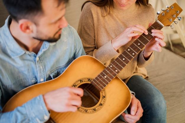 Alto ângulo de professor de violão, tutoria aluno em casa