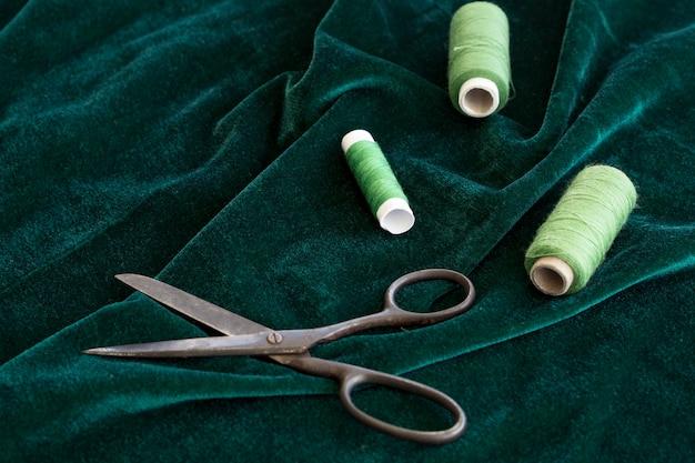 Alto ângulo de rolos de fio verde com veludo e tesoura