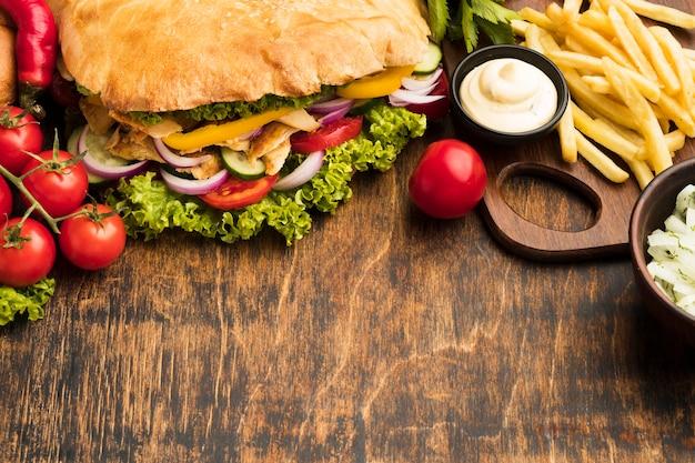 Alto ângulo de saboroso kebab com batatas fritas e espaço de cópia