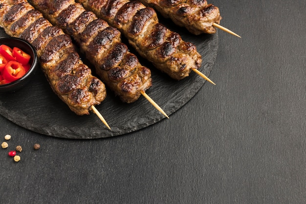 Alto ângulo de saboroso kebab na lousa
