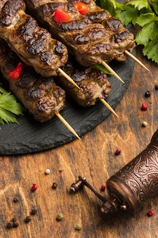 Alto ângulo de saboroso kebab no prato com condimentos