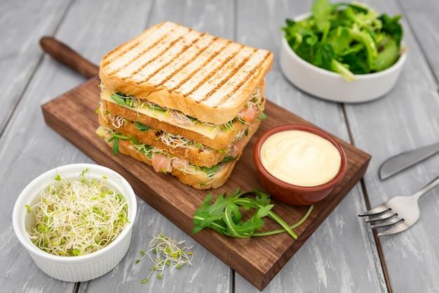 Alto ângulo de sanduíche delicioso com maionese e salada