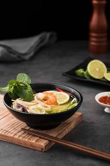 Alto ângulo de sopa com macarrão e pauzinhos