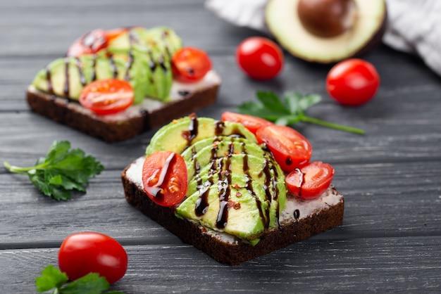 Alto ângulo de torrada de abacate com tomate e molho