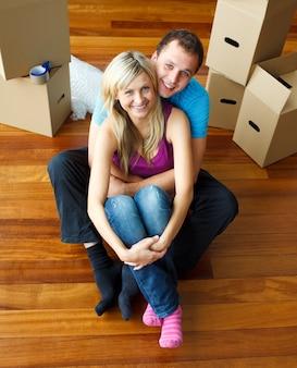 Alto ângulo de um casal sentado no chão. mudança de casa