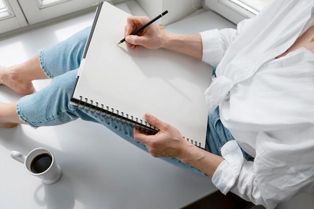 Alto ângulo de uma jovem desenhando em casa perto da janela