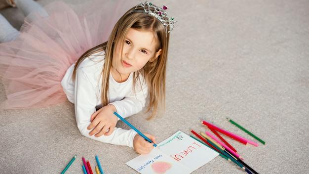 Alto ângulo de uma linda garota segurando um cartão de desenho para o dia dos pais