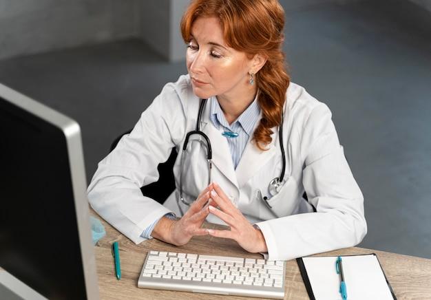 Alto ângulo de uma médica olhando para o computador em sua mesa