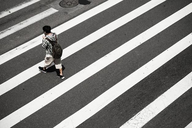 Alto ângulo de uma pessoa na faixa de pedestres