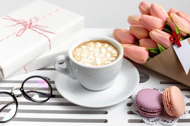Alto ângulo de xícara de marshmallows com tulipas e presentes