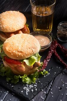 Alto ângulo delicioso procurando variedade de hambúrguer na chapa preta