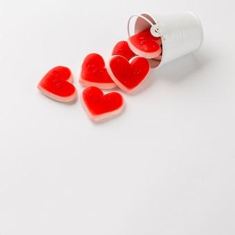 Alto ângulo do balde com doces em forma de coração e espaço para texto
