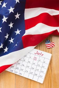 Alto ângulo do calendário do mês de julho e bandeiras americanas na superfície de madeira