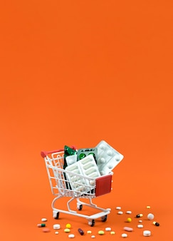 Alto ângulo do carrinho de compras com folhas de espaço e pílula de cópia