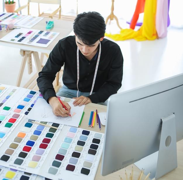 Alto ângulo do designer de moda asiático criando desenhos coloridos enquanto está sentado à mesa profissional