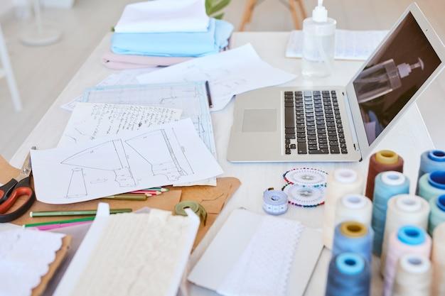 Alto ângulo do laptop com plano de linha de roupas e carretéis de linha na mesa do ateliê