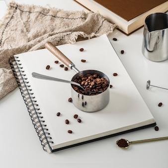 Alto ângulo do notebook com uma xícara de grãos de café torrados