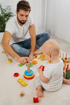 Alto ângulo do pai brincando com o bebê em casa