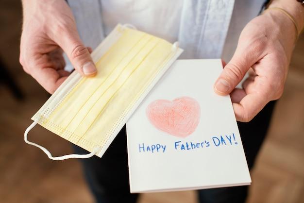 Alto ângulo do pai segurando seu cartão para o dia dos pais com máscara médica