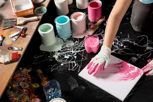 Alto ângulo do pintor com tela e latas de tinta