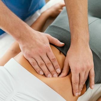 Alto ângulo do terapeuta osteopático masculino verificando o abdômen da paciente