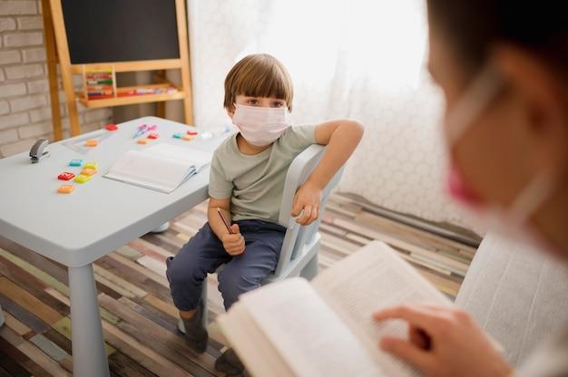 Alto ângulo do tutor com máscara médica, ensinando a criança em casa