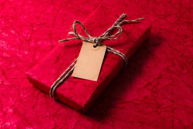 Alto ângulo embrulhado presente de natal com tag vazia
