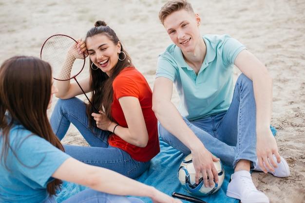 Alto ângulo feliz amigos com raquete e bola