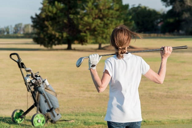 Alto ângulo feminino jogando golfe