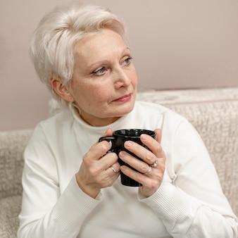 Alto ângulo feminino sênior em casa bebendo café
