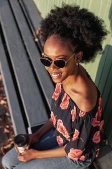 Alto, ângulo, jovem mulher africana, sentado num banco