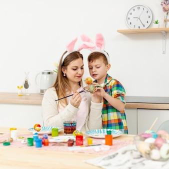 Alto ângulo mãe e filho com orelhas de coelho pintando ovos
