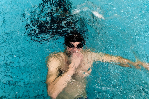 Alto, ângulo masculino, segurando a respiração debaixo d'água