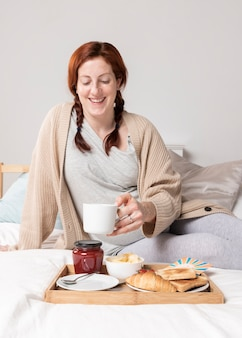 Alto, ângulo, mulher, desfrutando, brunch, cama