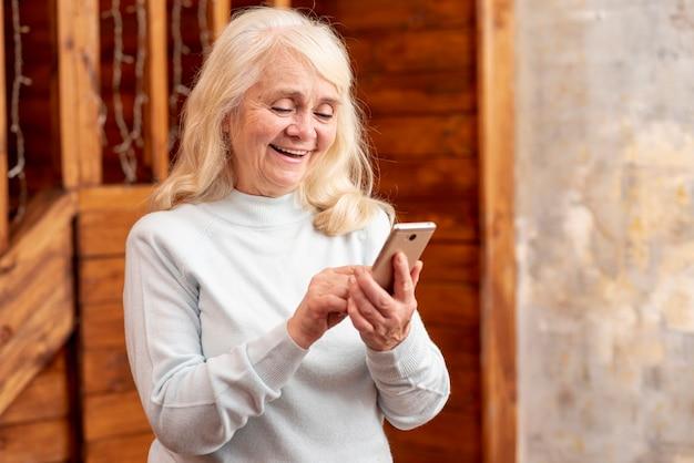 Alto, ângulo, mulher sênior, usando móvel