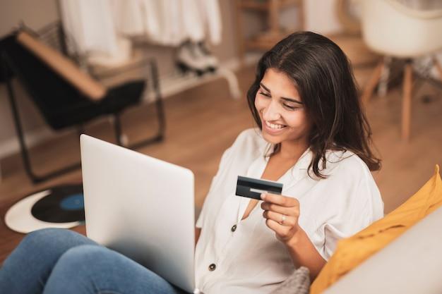 Alto, ângulo, mulher sorridente, segurando um cartão de crédito