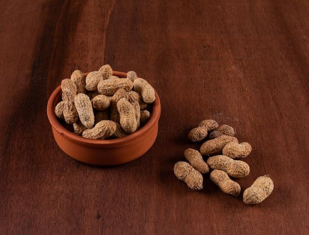 Alto ângulo vista amendoins crus em tigela na horizontal de madeira