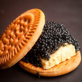 Alto ângulo vista preto caviar entre biscoitos com manteiga em fundo escuro.
