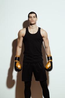 Alto desportista atraente posando em luvas de boxe