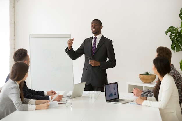 Alto-falante africano confiante ou treinador de negócios, dando a apresentação para a equipe
