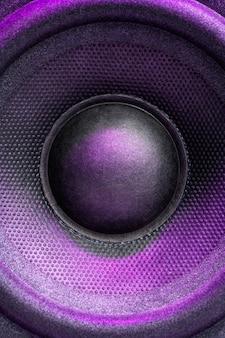 Alto-falante de áudio ou coluna de música com luz de fundo roxa, close-up. foto vertical