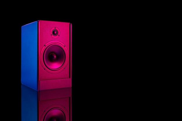 Alto-falante estéreo de cor neon em fundo escuro com reflexo. alto-falante de áudio com espaço de cópia