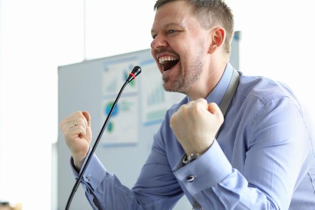 Alto-falante masculino apertou os punhos microfone frontal