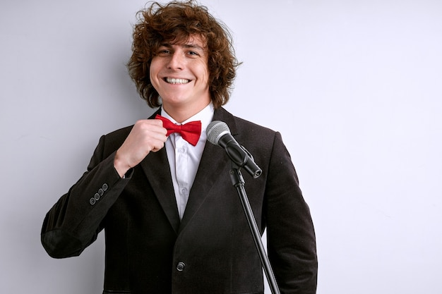 Alto-falante masculino confiante fixando uma gravata antes da apresentação com microfone, não tenha medo de falar em público, sorrindo
