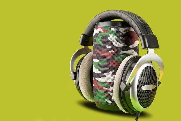 Alto-falante portátil e fone de ouvido em um fundo verde