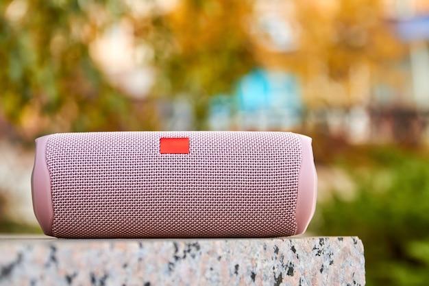 Alto-falante rosa portátil sem fio na cidade em superfície de granito