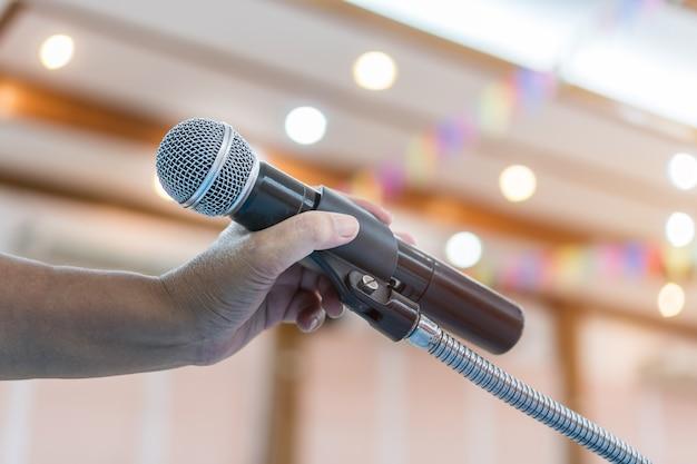 Alto-falante segurando o microfone para falar, apresentação no palco na sala de seminário de conferência pública.