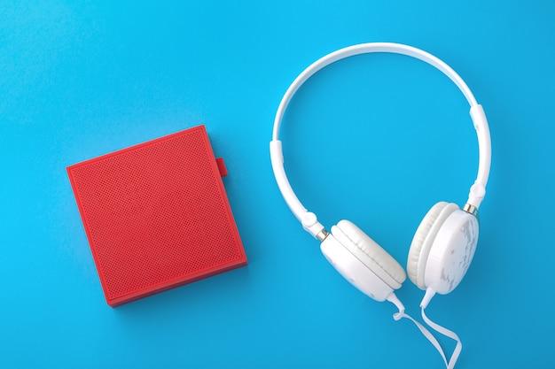 Alto-falante sem fio vermelho e fones de ouvido com fio brancos