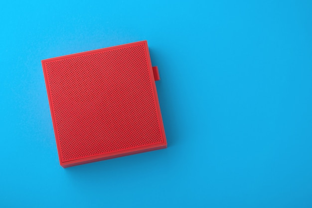 Alto-falante sem fio vermelho em fundo azul, minimalismo