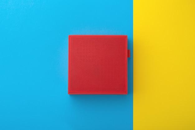 Alto-falante vermelho sobre fundo azul e amarelo